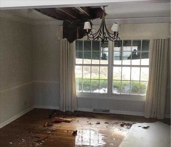 Wet floor of a dining room with the ceiling falling down and drywall on the floor.